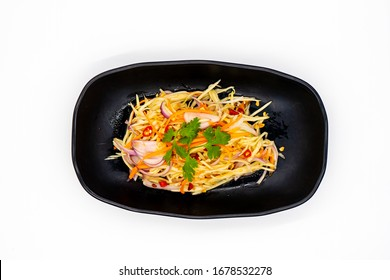 Spicy mango salad with vegetable and chili in black dish on white background, Famous authentic Thai food