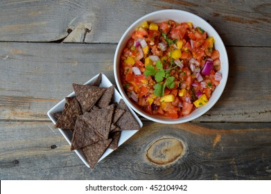 Spicy mango salsa with a bowl of tortilla chips