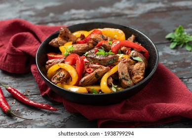 Spicy meat with peppers cooked in a wok. Pieces of chicken with red and yellow peppers in a black bowl on a dark background. Asian style food.