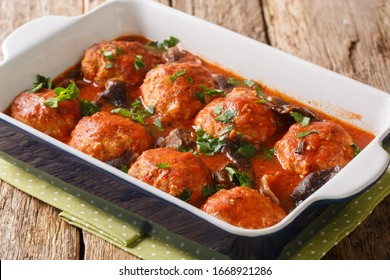 Spicy meatballs cooked with wild mushrooms in tomato sauce close-up in a baking dish on the table. horizontal