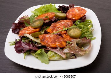 Spicy Mediterranean Salad of chorizo sausage with jalapeno chillis and herby salad leafs.