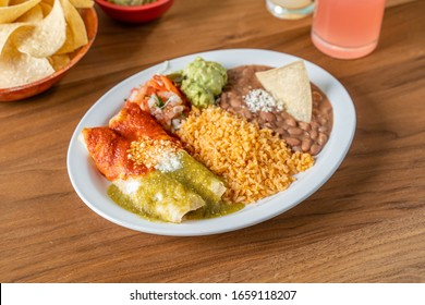 Spicy Mexican food in a restaurant. Christmas enchiladas with rice and refried beans.