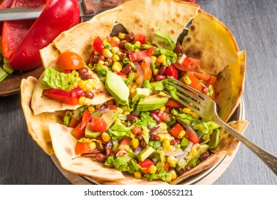 Spicy Mexican vegetarian taco salad with avocado, corn, pepper, tomatoes and beans
