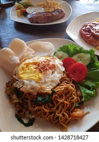 Spicy Mie/Mee Goreng Noodles with sunny side up egg on top of it, a famous cuisine in Indonesia