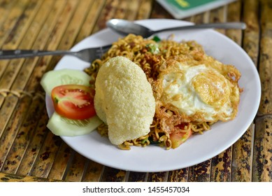 Spicy Mie/Mee Goreng Noodles with sunny side up egg on top of it, a famous cuisine in Indonesia and Malaysia. selective focus.