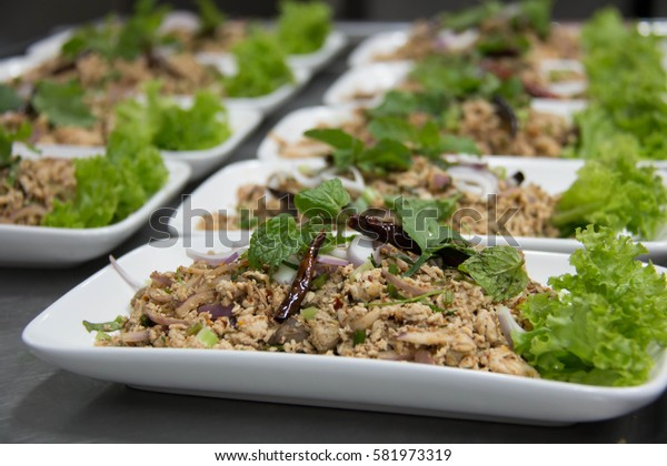 A Spicy minced pork salad with dried chili and garnished with mint.