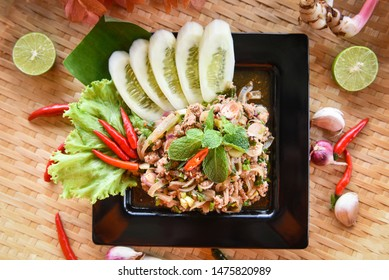 Spicy minced pork salad Thai food served on tray with herbs and spices ingredients / Tradition northeast food Isaan delicious on plate with fresh vegetables - Larb Pork Thai menu Asian food