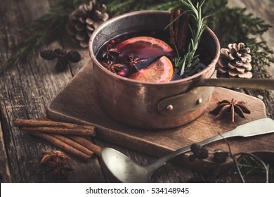 spicy mulled wine with orange, cinnamon and anise. rustic background, selective focus, toned.