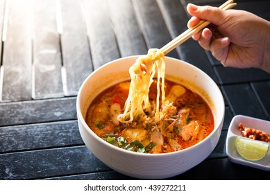 spicy noodle soup on black wooden background