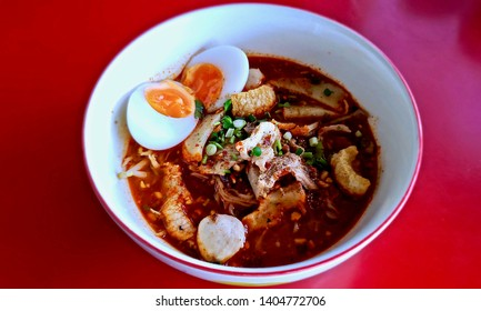 Spicy noodles soup with eggs,  pork balls,  liver, and pork stuff, wit Thai traditional ingredients, In Thailand this soup called 'Tomyum noodles soup""