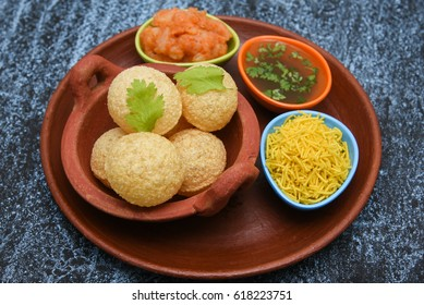 Spicy Pani puri golgappe served with yogurt, Chat item, India. Indian panipuri snacks eaten with tangy tamarind water and potato stuffing, North Indian street food Delhi, Mumbai, Rajasthan, Bangalore