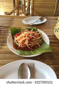 Spicy papaya salad on bamboo table