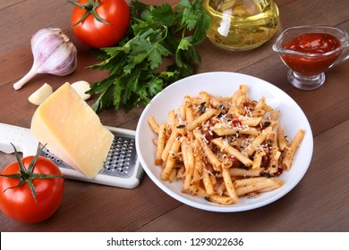 Spicy pasta penne bolognese with vegetables, chili and cheese in tomato sauce.