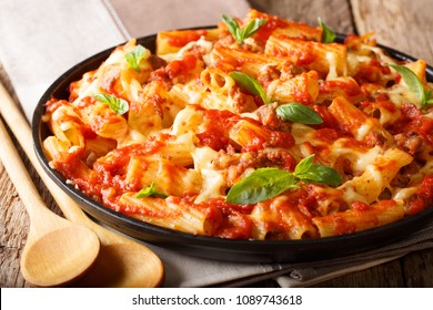 Spicy pasta ziti with minced meat, tomatoes, herbs and cheese close-up on a plate. horizontal