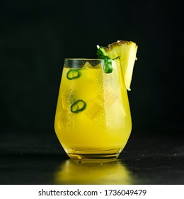 Spicy pineapple jalapeno mezcalita or margarita for Cinco de Mayo is a refreshing cocktail made with pineapple, cilantro, jalapeno and mexican distilled alcoholic beverage on black surface - Shutterstock ID 1736049479