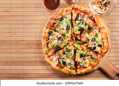 Spicy pizza with chicken gyros, green pepper, olives and onion on cutting board. Top view