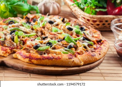 Spicy pizza with chicken gyros, green pepper, olives and onion on cutting board