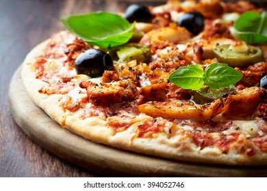 Spicy Pizza with Chicken Gyros, Mozzarella, Jalapeno Pepper, Black Olives,  Spices and Fresh Basil. Italian pizza. Home made. Concept for a tasty and hearty meal. Rustic wooden background.  Close up.
