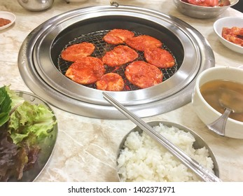 Spicy pork BBQ (Dweji Bulgogi) is barbecue ,barbeque set by cooking marinated pork meat on hot sizzling pan with fire charcoal that famous traditionall cuisine in Korean restaurant ,South Korea