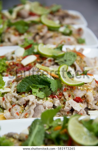 A Spicy pork salad with dried chili and garnished with mint.