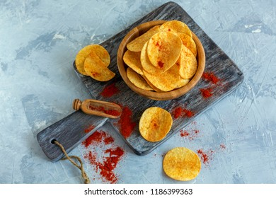 Spicy potato chips with paprika and sea salt in a wooden bowl on the serving board. Top view.