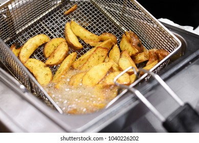 Spicy potato chips or wedges cooking in a deep fryer in a close up view of the hot bubbling oil and wire metal basket