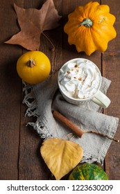 Spicy pumpkin latte with cinnamon and autumn leaves on wooden background