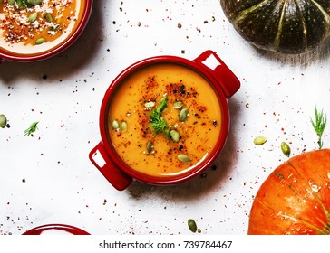 Spicy pumpkin soup in red pan, white background, top view