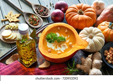 Spicy pumpkin soup seasoned with ginger and garlic, served in a hollowed pumpkin with croutons, parsley and cream. Autumn food background, text space.