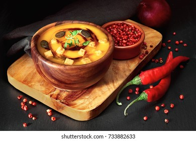 Spicy pumpkin soup in wooden bowl on dark background, served with pumpkin oil, pumpkin seeds, croutons and thyme leaves. This is German variation of pumpkin soup.