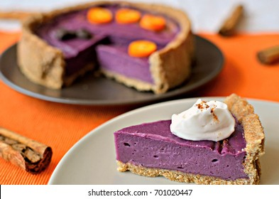 Spicy purple yam pie with coconut whip. This pie is vegan, gluten-free and sugar-free. Slice on a white plate. Orange background