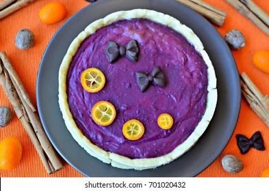 Spicy purple yam pie. This pie is vegan, gluten-free and sugar-free. Top view. Orange background