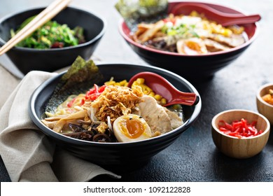 Spicy ramen bowls with noodles, pork, chicken, boiled egg and vegatables served with seaweed salad