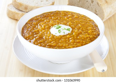Spicy red lentil soup with yoghurt and bread, in a white  bowl.