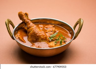 Spicy Reddish Chicken Curry / Masala, with prominent Leg Piece, served in a bowl, accompanied by Pilau Rice, Chapati/Roti and salad. Served over colourful or wooden background. selective focus.