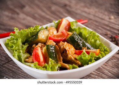 Spicy salad with chili cucumbers in a white plate on a wooden background