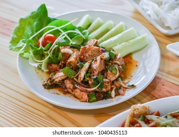 Spicy salad with Roasted Pork on Wooden Table
