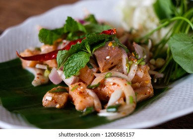 Spicy salmon salad. Thai style fusion food. East meets West food.Raw salmon salad with spicy and sour dressing on banana leaf with mint leaves on top.