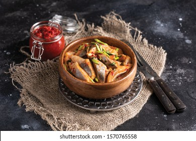 spicy salted herring with red pepper paste and green onions in a wooden plate