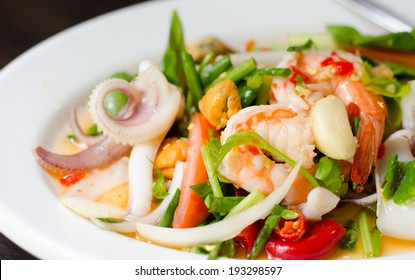 Spicy sea food salad served in white plate.
