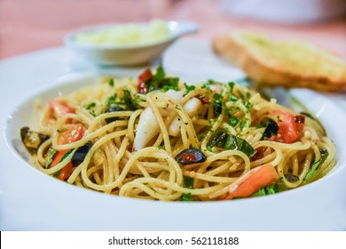 The spicy seafood spaghetti serve with garlic bread and cheese
