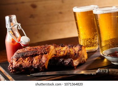 Spicy seasoned grilled spare ribs with two tall glasses of cold beer served with ketchup and chutney on a tray in a tilted angle