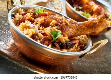 Spicy seasoned kabsa Arabian food bowl with assorted vegetables and meat in long grained Basmati rice garnished with fresh herbs in a tilted angle view
