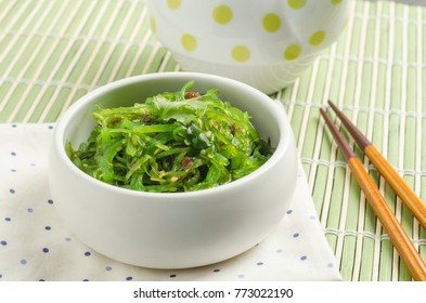 Spicy Seaweed Salad with chopsticks on bamboo background.