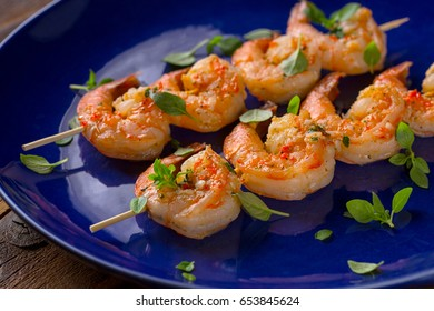 spicy shrimp skewers served on blue plate