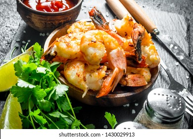 Spicy shrimps in a bowl with slices of lime, parsley and sauce. On black rustic background