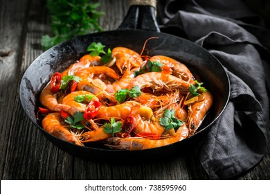 Spicy shrimps on pan with garlic, coriander and peppers
