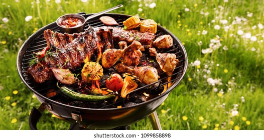 Gewürzige Rippen, verschiedene Veggies und Hühnertrommeln, die auf einem tragbaren Grill im Freien auf einer Federwiese mit Lüstern im Panoramaformat grillen