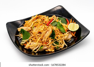 Spicy stir fried instant noodle with chicken and holy basil leaves in black dish on white background.