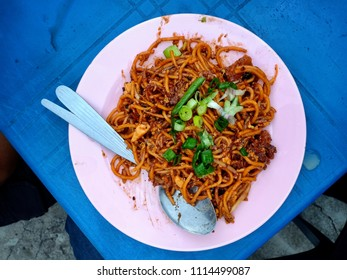 Spicy stir fried noodles with veggies and assortment of asian sauces served on blue  table. Known as Mee Goreng / Mi Goreng in Malaysia, Singapore and Indonesia.
